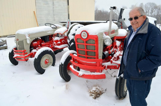 Charlie Bates stands next to two of the first tractors he ever purchased.