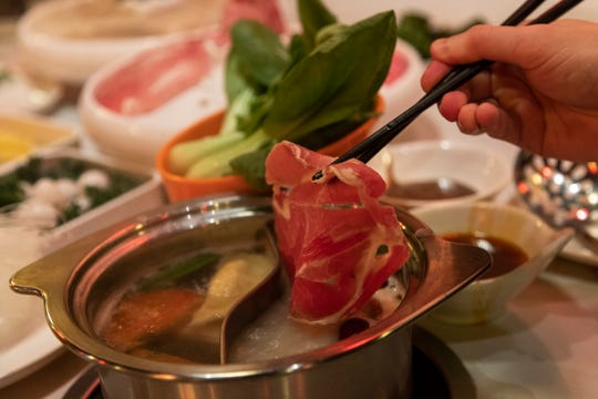 Dipping a thin sliced lamb in boiling clear soup hot pot at Lao Pot in Madison Heights, Thursday, Feb. 6, 2020.