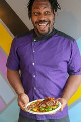 Yum Village chef-owner Godwin Ihentuge poses with a lamb shank at his Detroit restaurant.