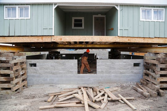 In this Wednesday, Jan. 8, 2020, photo, laborer Logan Farrington works under a house being lifted in Luna Pier, Mich. The project will protect the home from the potential rising lake levels of Lake Erie.
