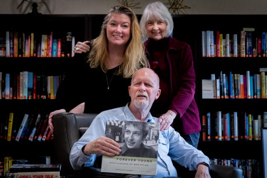 Photographer Douglas R. Gilbert poses with daughter Anne Carpenter and wife Barbara Gilbert, while displaying a book of his photographs of a young Bob Dylan from 1964.