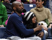Kobe Bryant and his daughter Gianna watch the first half of an NCAA college basketball game between Connecticut and Houston in Storrs, Conn. on March 2, 2019.
