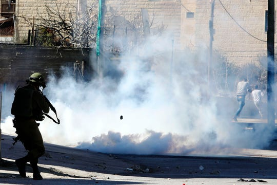 Israeli soldiers fire tear gas towards Palestinians during clashes in the West Bank city of Bethlehem, Thursday, Feb. 6, 2020. Israeli forces have killed two Palestinians in clashes in the occupied West Bank and a third in Jerusalem after he opened fire at a police officer.