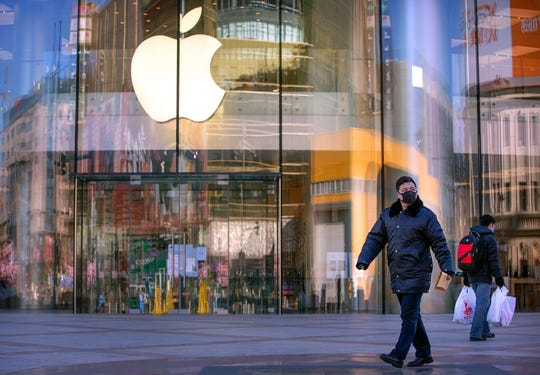 In this Feb. 4, 2020 photo, people wearing face masks walk past an Apple store in Beijing that was closed, along with all of Apple's other stores in China, due to health concerns amid a virus outbreak.