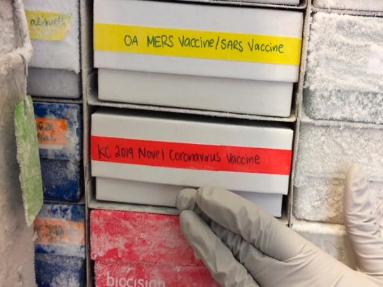 In this undated frame from video provided by the National Institute of Allergy and Infectious Diseases (NIAID), a scientist returns a novel coronavirus vaccine sample to a freezer in Bethesda, Md.