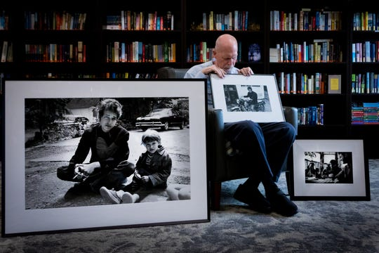 Douglas R. Gilbert displays photographs he made of Bob Dylan back in 1964. The large photo in front is of Bob Dylan behind the Cafe Espresso in Woodstock, NY with the daughter of Bernard and Mary Lou Paturel (owners of the cafe). The photo being held is Bob Dylan on a Triumph, behind Cafe Espresso, Woodstock, NY.