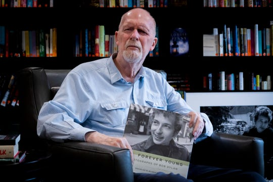 Douglas R. Gilbert holds the book, Forever Young-Photographs of Bob Dylan, which he created with Dave Marsh of Rolling Stone Magazine.