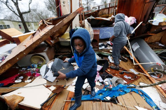 Emma Carter's grandsons comb the remains of her mobile home in Pickens, Miss., looking for salvageable clothing and personal items after severe weather hit the area, Thursday, Feb. 6, 2020. None of the other mobile homes adjacent to the Carter's were destroyed when the winter storm hit Wednesday.
