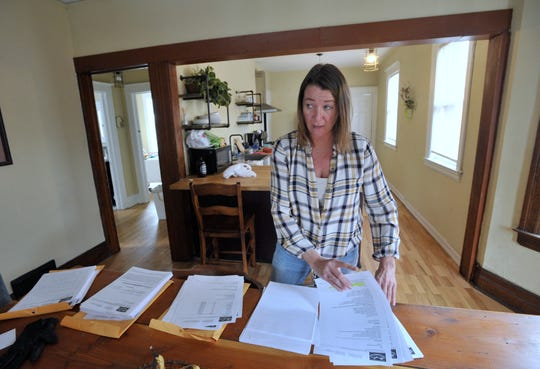 Tracey Hart, 48, of Riverside, Calif., goes through paperwork as her ex-husband, Johnny Guzman (not pictured), 46, of Eastpointe, listens.