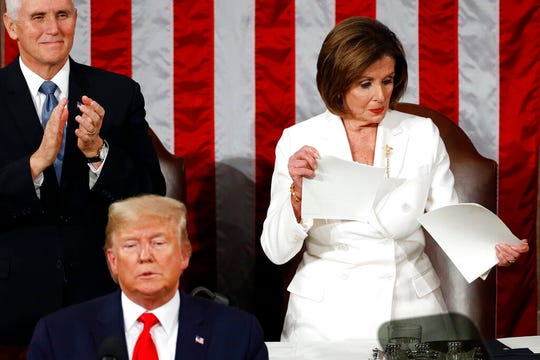 House Speaker Nancy Pelosi of Calif., tears her copy of President Donald Trump's s State of the Union address after he delivered it on Tuesday, Feb. 4, 2020. Vice President Mike Pence is at left.