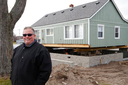 In this Wednesday, Jan. 8, 2020, photo, homeowner Jim Bozynski stands outside his house that is being lifted in Luna Pier, Mich. The project will protect the home from the potential rising lake levels of Lake Erie.