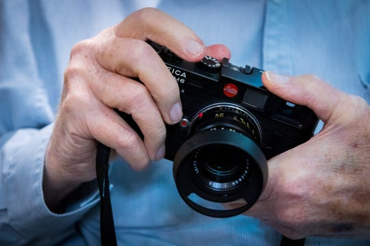 Photographer Douglas R. Gilbert holds his Leica M6 camera at his home in Grand Haven, Michigan.