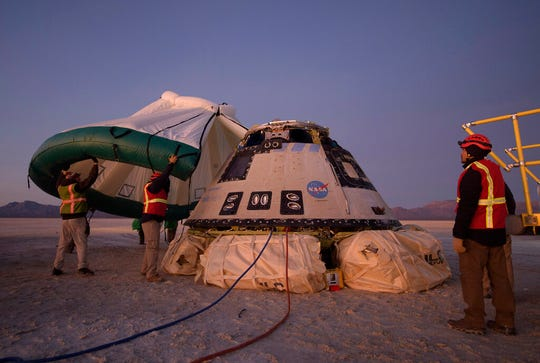 Boeing, NASA, and U.S. Army personnel work around the Boeing Starliner spacecraft shortly after it landed in White Sands, N.M. on Dec. 22, 2019.