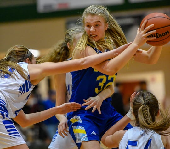 Castle's Natalie Niehaus (32) battles a host of Memorial Tigers defenders during the Southern Indiana Athletic Conference tournament championship at North High School, Saturday evening, Jan. 18, 2020.