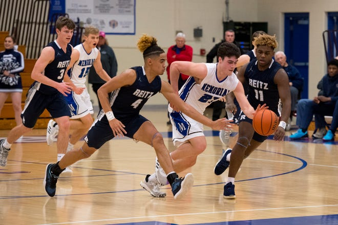 Reitz's Khristian Lander (4) attempts to steal from Memorial's Cade Graham (21) during the Memorial Tigers vs Reitz Panthers game at Robert M Kent Athletic Center in Evansville, Ind., Thursday evening, Feb. 6, 2020.