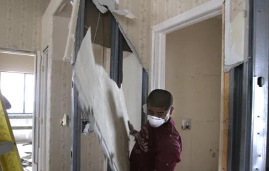 Worker removes China-manufactured drywall from a Southwest Florida home. The drywall is blamed for emitting hazardous fumes that made people sick and buildings uninhabitable. A federal lawsuit over the drywall has been settled.