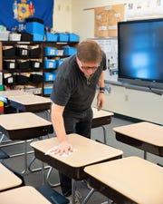 Oconto Elementary teacher Dave Niswonger disinfects his 4th grade classroom desks on Friday.
