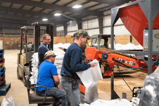 Oconto County employees on Friday fill sandbags at the County Recycling Center in Oconto, using a machine leased from Brown County. The county plans to keep 10,000 sandbags on hand for residents and municipalities needing to protect against expected flooding this spring.