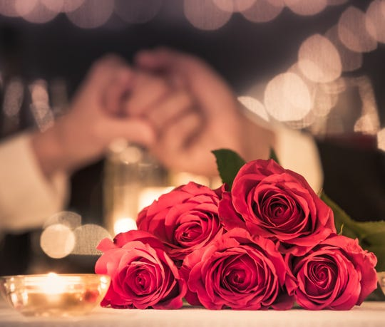 Couple at a candle light dinner date holding hands next to bouquet of red roses.
