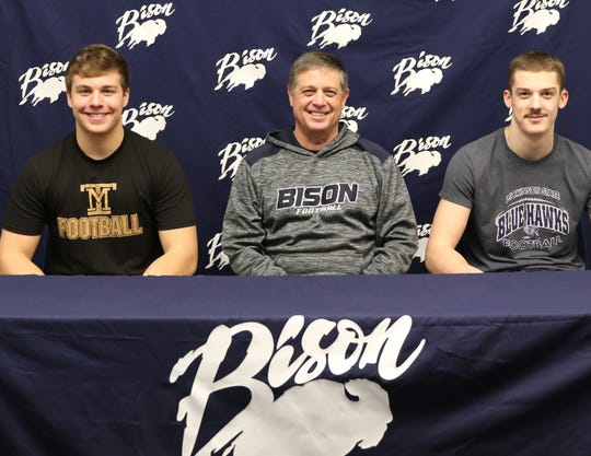Great Falls High's Andrew Almos, left, and Tyson Krahe, right, are pictured with Bison head football coach Mark Samson. Almos and Krahe signed Friday to play college football at Montana Tech and Dickinson State, respectively.