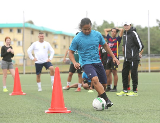 "Community First/Days Inn Dededo Soccer Club coach Roy Santos takes part in the dribbling portion of the coaches skills test as GFA technical director and course instructor Sang Hoon Kim, in white hat, observes his technique during the Guam Football Association ""D"" License Course, held at GFA from Feb. 1-3 at the Guam Football Association National Training Center."