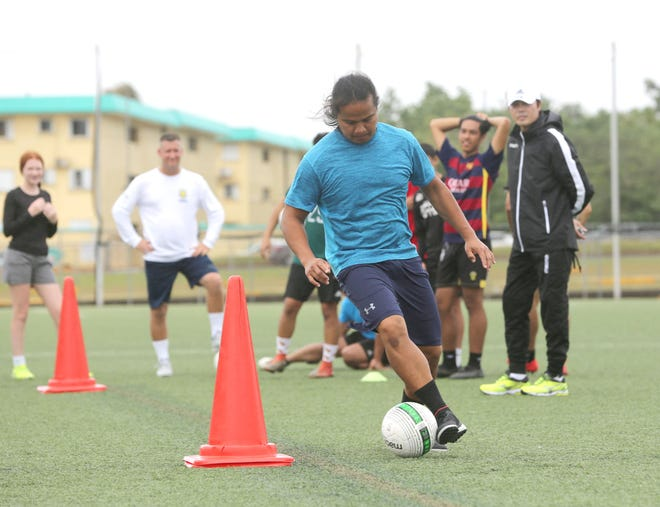 """Community First/Days Inn Dededo Soccer Club coach Roy Santos takes part in the dribbling portion of the coaches skills test as GFA technical director and course instructor Sang Hoon Kim, in white hat, observes his technique during the Guam Football Association """"D"""" License Course, held at GFA from Feb. 1-3 at the Guam Football Association National Training Center."""