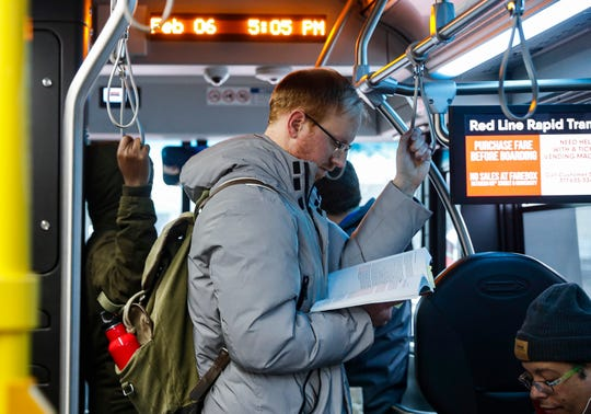 Passenger Danny Kerns reads a book while standing on the IndyGo Red Line, Indianapolis, Thursday, Feb. 6, 2020.