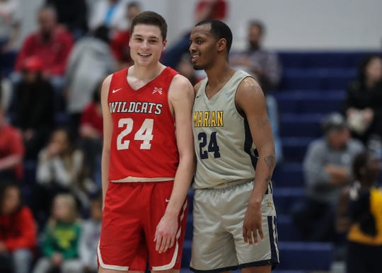 Indiana Wesleyan Wildcats Kyle Mangas (24) and Marian Knights Tyrie Johnson (24) have a laugh before the start of overtime at Marian University on Feb. 1, 2020.