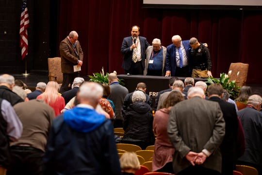 Church security panelists pray as they end their discussing about keeping churches secure from threats of active shooters.