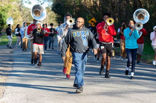 Northside High School Marching Band Director Alex Thomas leads his students down a neighborhood street near the school Feb. 7, 2020, preparing to march in upcoming Mardi Gras parades.