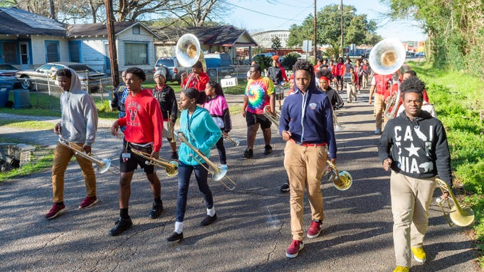 Members of the Northside High School Marching Band and Auxiliary use a neighborhood near the school to work on pacing and staying in formation as they practice Feb. 7, 2020. They will perform in five Mardi Gras parades in February.