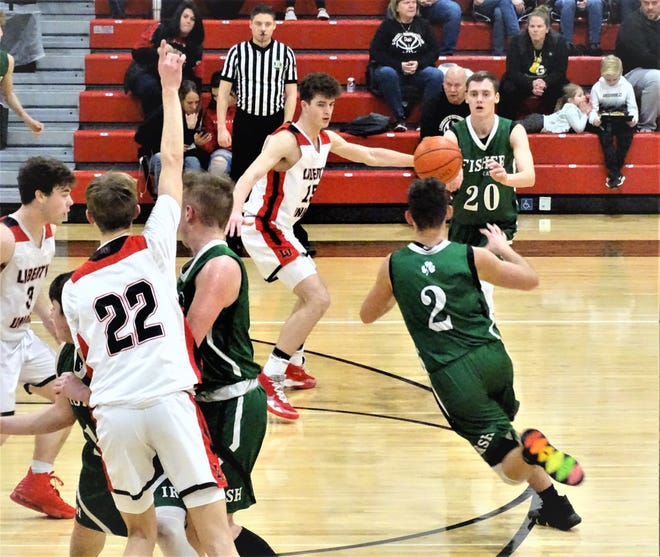 Fisher Catholic's Bryson Vogel makes a pass to a cutting Kaden Starcher during the Irish's 79-61 loss at Liberty Union Thursday night.