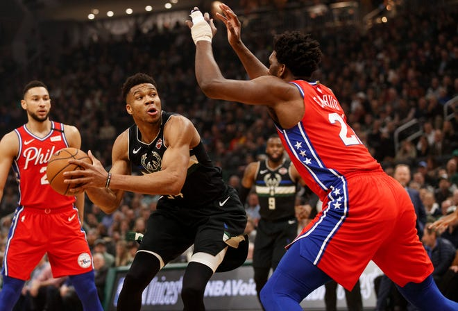 Feb 6, 2020; Milwaukee, Wisconsin, USA;  Milwaukee Bucks forward Giannis Antetokounmpo (34) drives against Philadelphia 76ers center Joel Embiid (21) during the first quarter at Fiserv Forum. Mandatory Credit: Jeff Hanisch-USA TODAY Sports