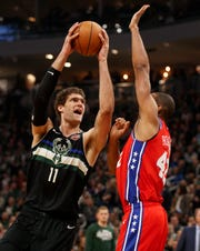 Bucks center Brook Lopez looks to shoot despite the defense of  76ers forward Al Horford Thursday night.