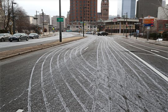 Stripes from an ice melting mix are left on the road after being applied along West Kilbourn Avenue at North Old World Third Street looking east. The mix is more efficient than regular road salt, officials say.