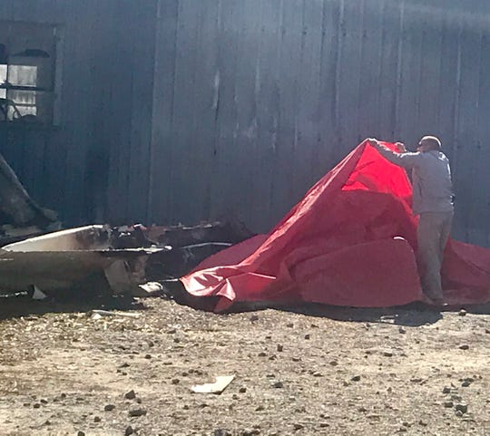 A Jackson Parish sheriff's removes a tarp from the plane wreckage Friday.