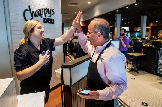 David Barranco, right, gives a high five to employee Mallory Wright after she announced that she has become an RN at Chappy's Deli in Montgomery, Ala., on Friday February 7, 2020.