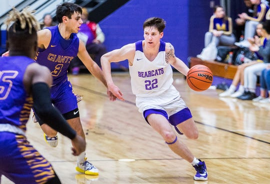 Central's Dylan Stafford dribbles around a Marion defender during their game at the Muncie Fieldhouse Thursday, Feb. 6, 2020.