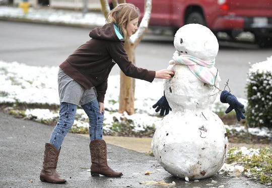 2 Chloe Evans,11, makes a snowman at her outside her home in Franklin, Tenn., on Friday, Feb. 7. This week's wintry weather in central Ohio might be good for snowman-making.
