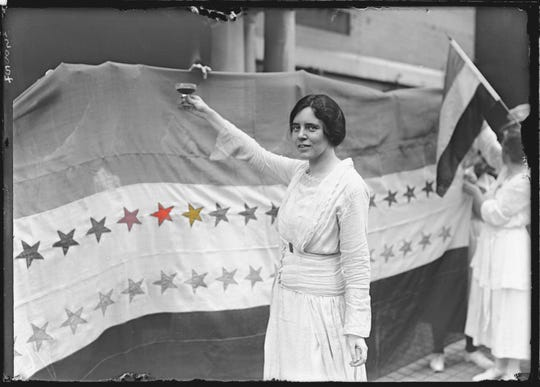 Alice Paul makes a toast to Tennessee's ratification of the 19th Amendment to the U.S. Constitution, giving women the right to vote. The banner beside her was displayed outside the National Women's Suffrage Party Washington, D.C., headquarters showing the stars of the states which had ratified the amendment.