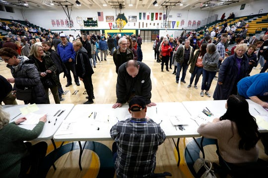 Local residents check-in after arriving at an Iowa Democratic caucus at Hoover High School, Monday, Feb. 3, 2020, in Des Moines, Iowa.