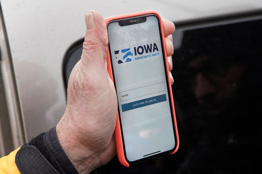 Precinct captain Carl Voss of Des Moines displays the Iowa Democratic Party caucus reporting app on his phone outside of the Iowa Democratic Party headquarters in Des Moines, Iowa, Tuesday, Feb. 4, 2020.