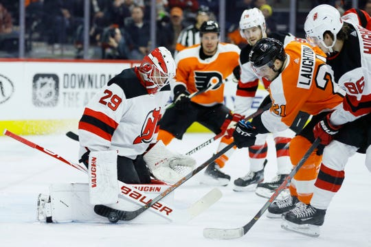 Philadelphia Flyers' Scott Laughton (21) cannot get a shot past New Jersey Devils' Mackenzie Blackwood (29) as Jack Hughes (86) defends during the second period of an NHL hockey game, Thursday, Feb. 6, 2020, in Philadelphia.
