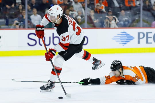 New Jersey Devils' Pavel Zacha, left, shoots the puck past Philadelphia Flyers' James van Riemsdyk during the first period of an NHL hockey game, Thursday, Feb. 6, 2020, in Philadelphia.