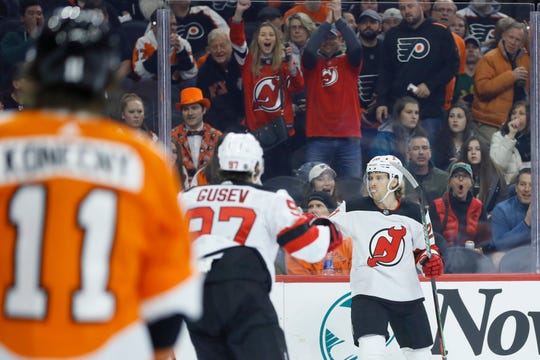 New Jersey Devils' Blake Coleman (20) celebrates with Nikita Gusev (97) past Philadelphia Flyers' Travis Konecny (11) after Coleman scored a goal during the first period of an NHL hockey game, Thursday, Feb. 6, 2020, in Philadelphia.