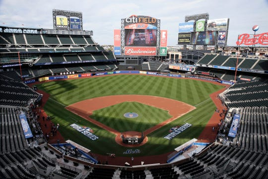 FILE - In this Oct. 29, 2015, file photo, members of the media and grounds crew work on the field at Citi Field in New York, the day before Game 3 of the World Series between the Mets and the Kansas City Royals at the stadium. Baseball Commissioner Rob Manfred says talks have ended over the proposed sale of a controlling share of the Mets from the families of Fred Wilpon and Saul Katz to hedge fund manager Steven Cohen.
