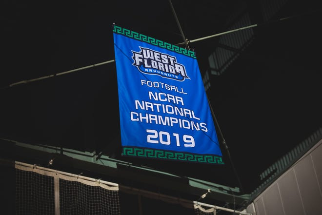 The University of West Florida football team's NCAA Division II championship banner is raised in UWF Field House on Thursday, Feb. 6, 2020.