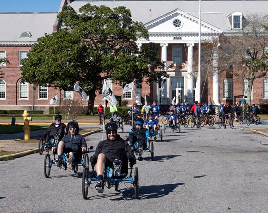Cyclists taking part in the Wounded Warrior Project Soldier Rideat Naval Air StationPensacola on Friday pass by Building 633, where the deadly shooting took place Dec. 6.