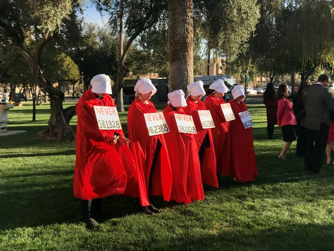 Women dressed as characters from the Handmaid's Tale, a dystopian novel in which women are stripped of their rights and used for reproduction, protest Senate Bill 1328 and House Bill 2388 outside the House of Representatives on Thursday, Feb. 6, 2020. The mirror bills would tie funding for the state's crisis hotline to creation of an anti-abortion program.