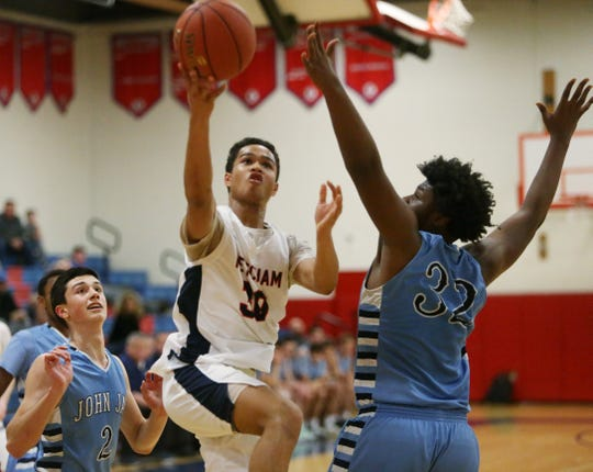 Ketcham's Phoenix Bowman goes in for a layup over John Jay's Wesley Fulcher during Thursday's game boys basketball game.